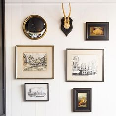 Gallery wall of small vintage artwork, mounted antlers, and a round mirror.