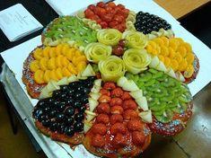Tarta en forma de flor y cada petalo de una fruta fresca.