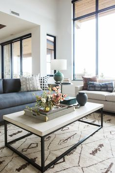 How to style a coffee table like a pro If your living room is short on space, buy a coffee table without a bottom shelf - it visually takes up less space. Great room with dramatic stone fireplace, layered rugs, and neutral color scheme