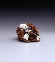 Hoshu, Sleeping Hotei,  late 19th century,  wood, ivory, and silver,  ht. 1 in (2.5 cm)  The Toledo Museum of Art
