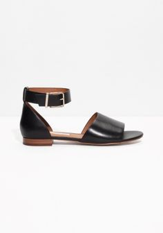 These dainty sandals are styles from smooth shiny leather and feature a simple open-toe design offset by a wide ankle strap with gold-tone buckle.
