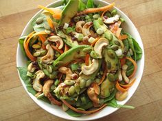 Spinach salad with carrot, avocado, roasted cashews, pumpkin seeds, green onion, and a balsamic vinaigrette.