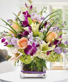"""""""Pour L' Amour Bouquet"""" - Purple dendrobium orchids are set in contrast with peach roses and green hydrangea. Just bursting with life and, as the title suggests, """"For Love!"""" This arrangement will warm the heart of its lucky recipient."""