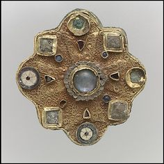 Frankish Disk Brooch  from the second half 7th century, made in Gold sheet, filigree, moonstone/adularia, glass cabochons, garnets, mother-of-pearl, and moonstone.
