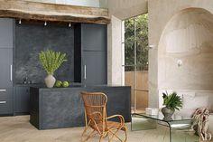 La cocina abierta de la casa de Malibú del diseñador y antiquario Richard Shapiro está protagonizada por una isla hecha de basalto. La misma piedra volcánica se utiliza para la pared posterior y la encimera, los muebles son lacados en negro.