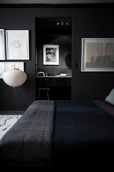 Dark bedroom with black walls and framed white art