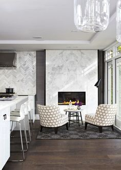 Sleek marble fireplace surround, as well as marble subway tiles laid in a herringbone pattern on the wall