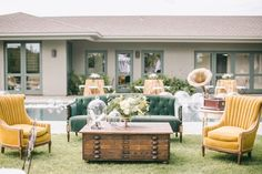 1920s inspired lounge area complete with mustard yellow chairs and a emerald couch