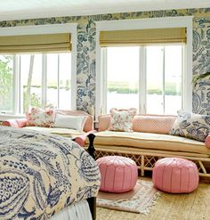 This master bedroom has an abundance of windows in order to take in coastal views. Large-scale print wallpaper and matching bedding gives the space a cozy feeling, while a woven rug and Roman shades balance the dramatic blue print.