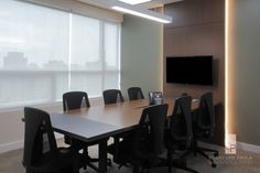 STUDIO CRIS PAOLA: Sala de reunião em escritório no Morumbi, painel com TV e iluminação atrás garante a sofisticação das reuniões. Projetado pela arquiteta Cris Paola #studiocrispaola #sp #iluminação #corporativo #corporativeinterior