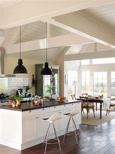 Cocina con isla de encimera de madera y lámparas tipo industrial
