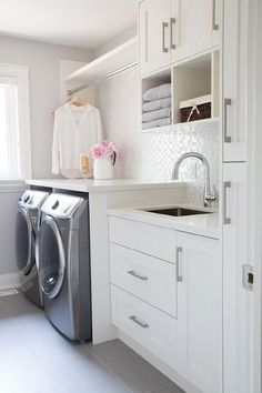 Gorgeous laundry room features  a built-in clothes rod over an enclosed washer and dryer alongside a gray slate staggered tiled floor.