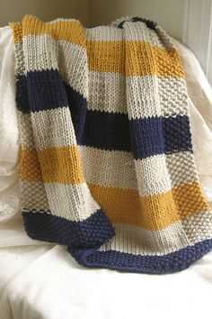This is a hand knit baby blanket in navy, cream, and mustard colors. The blanket is knit from machine wash and dryable yarn, a must have for an infant. The blanket measures approximately 3ft long by 2 ft wide, making it the perfect size for wrapping up your new one, or keeping warm in a