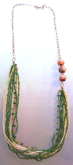 Asymmetric necklace with green seed beads and red/silver lampwork beads