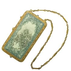 """Lot 2016 - FINE SCENIC GUILLOCHE ENAMELED GOLD NECESSAIRE - Estimate: $3,000 - $5,000  The rectangular cushion shaped necessaire with opalescent celadon and blue enameled engraved scenic reserves, ivy vine engraved edges, sapphire thumbpress reveals three chambered, intricately engraved interior compartment, fancy fetter link chain. Unmarked, above 14k. 2 3/4"""" x 1 1/2"""", chain 19"""". 61.6 dwt."""