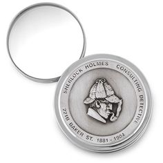 """Sherlock Holmes Desk Magnifier - Whatever you're looking at is easier to see when this handsome pewter instrument makes it appear three times larger than life. Perfect for examining small clues, reading tiny print and following in the hallowed footsteps of the Master Detective. Cleverly disguised as an embossed medallion desk ornament, it goes into action the instant you swivel the glass from its case. Hand-finished, 100% British pewter. 2 3/8"""" diameter x 5/8""""h."""