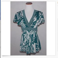 """BcbgMaxAzria green&white top BCBG floral green and white blouse with a tie at the back.  Good gently pee-owned.  Smoke free home.  Measurements:. 26"""" long from shoulder to bottom hen;. 14"""" wide from armpit to armpit. Sleeve is 9"""" long.  Size small.  Make me an offer.  Bundle and save! BCBGMaxAzria Tops Blouses"""