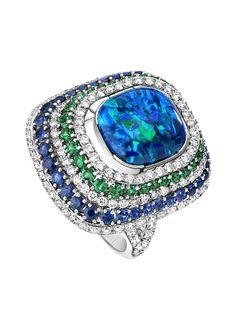 Bague or blanc 18K opale noire, diamants taille brillants, 40 saphirs bleus ronds, émeraudes rondes.   White gold ring 18K, 1 black opal, brilliant-cut diamonds, 40 blue round sapphires, round emeralds. - Extremely Piaget