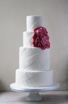 This simple white cake is accented with woven textured details and an oversized pink rosette.