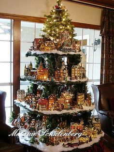 A cool way to display Christmas villages. d <>< Shelves in shape of Christmas tree to display Christmas collectibles, with small tree on top shelf. This is amazing! Noel Christmas, Christmas Projects, Winter Christmas, Christmas Ornaments, Modern Christmas, Christmas Greenery, Festa Party, Christmas Villages, Christmas Houses