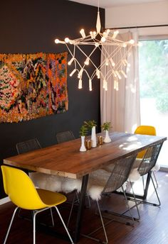 "This modern dining room is daring without crossing the line. We love the light fixture, it could be considered ""honest design"" by how it exposes its wires and light bulbs. The rustic wood table adds warmth and the Eames style molded chairs a fun pop of happy yellow for color. You also can't miss the funky, chunky textured textile wall decor against the black painted wall."