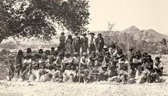 Native American (Paiute) men, women and children pose for a picture near a tree.