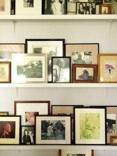 Shelves of family photos, all shapes, sizes, frames. love!