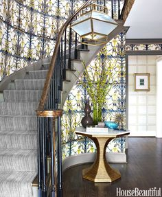 For a dramatic stairway, upholster the walls in a graphic fabric.