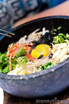 Traditional South Korean food called bibimbap - spicy vegetables mix with egg served in hot stone bowl.
