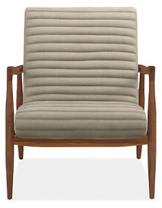 The striking Callan chair has details you'll appreciate from every angle. The contoured seat and back seem to float inside the frame, while horizontal channels add extra comfort. Available in three finishes, the solid wood frame offers an elegant profile with its soft curves and sophisticated tapered shape. It's a perfect place to relax.
