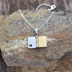 Darling book necklace with three turnable golden pages, on a silver chain.