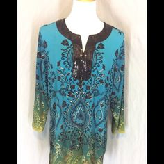 NWOT JM Collection Woman Tunic New with out tags, no defects. Polyester, Spandex blend. Blue that fades to teal that fades to green. Gold outlines of black designs. Black sequin design around the Neck in front if Bly. 3/4 sleeves. Very pretty piece. Bust 26 inches. Length 31 inches. JM Collections Tops Tunics