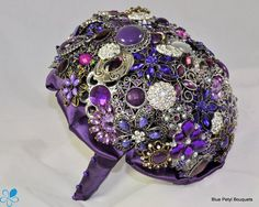 Purple Brooch Bouquet - Blue Petyl Bouquets This brooch bouquet features purple, violet, and lavender brooches, rhinestones, and Czech crystal accents. The bouquet is finished with a purple ribbon collar and handle.