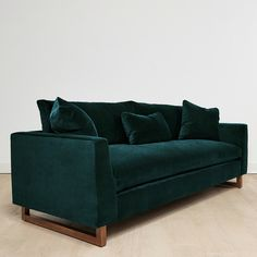 Lounge in luxury with this plush velvet sofa. Oversized cushions and three complementing throw pillows create an inviting set up, while angular wooden legs add a level of overall sturdiness to this piece.