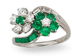 An emerald and diamond ring, Oscar Heyman & Brothers for Cartier of crossover design, centering two floral clusters of alternating round brilliant-cut diamonds and circular-cut emeralds completed by scrolling lines of baguette-cut diamonds and calibré-cut emeralds; signed Cartier, no. 63599 and 16562, with signed Cartier box; mounted in platinum.