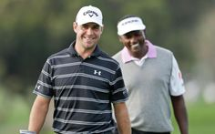 Gary Woodland, left, and Vijay Singh, right, joke as they arrive on the 9th green of the north course during the first round. (Gregory Bull/AP)