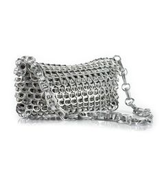 """Clutch shoulder bag with drop in chain strap.      Hand crocheted with over 400 post-consumer recycled pop tops.     Lightweight and expandable aluminum shell. Fully lined with beautiful silver satin interior     Zip closure     Size: 9""""L x 4""""H x 1""""D     Strap Drop: 11""""     Color: Metallic silver onl"""