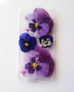 A clear, hard snap on iPhone 6 plus case with beautiful pressed flowers from my garden. The pansies have multiple shades of purple, magenta,