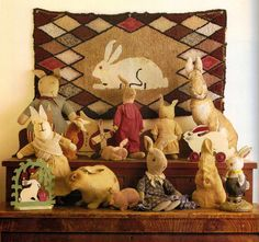 Vintage stuffed rabbits displayed in front of a rabbit design hooked rug