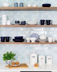 Open kitchen shelving with light blue subway splash back.
