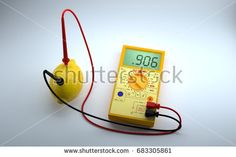 "Lemon battery on white background. Multimeter with positive and negative electrodes inserted into a lemon measures the ""bio electrical current"" created a fresh picked lemon. 3D Render."