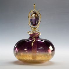 A perfume bottle of purple and gold blown glass by Joanne Gowan. The stopper is an ametrine gem wrapped in gold wire.