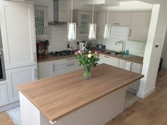 Howdens Burford stone kitchen with island and pendant lights.