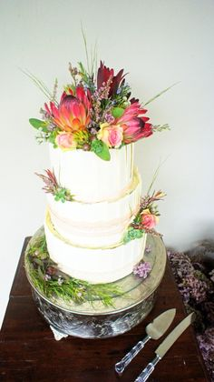 Decorated with Proteas, roses and fynbos, covered in white Belgium disks with a dark chocolate center.  A decadent wedding cake indeed.