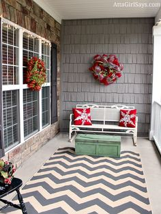 side porch decorated for Christmas with snowflake pillows and gray chevron rug and antique toolbox from AttaGirlSays.com