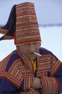 A Saami man in traditional costume smokes a cigarette, Kautokeino, northern Norway. | © Anders Ryman