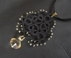 Black tatted lace pendant - lace motive with faceted teardrop - rosette with light gold colour beads
