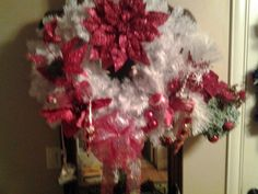 White wreath w/ red glittered flowers and red bow.