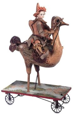 "*RARE ~ French Mechanical pull toy ""Polichinelle Riding an Ostrich"". Bisque headed Polichinelle doll is seated upon a paper mache ostrich."