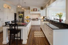Large open kitchen with traditional styled appointments. White cabinetry and island stand below dark marble countertops.